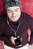 Hombre joven sonriente en un suéter y un casquillo que sostienen smartphone con los auriculares en línea Imagenes de archivo