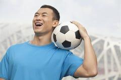 Hombre joven sonriente en una camiseta azul que sostiene el balón de fútbol en su hombro, al aire libre en Pekín, China Fotos de archivo libres de regalías
