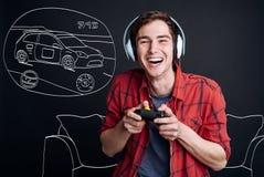 Hombre joven sonriente extático que juega a los videojuegos Fotografía de archivo libre de regalías