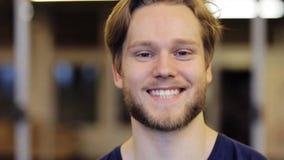 Hombre joven sonriente feliz con la barba en el gimnasio almacen de metraje de vídeo
