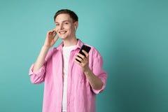 Hombre joven sonriente feliz en camisa rosada que habla en el teléfono móvil usando los auriculares inalámbricos foto de archivo libre de regalías