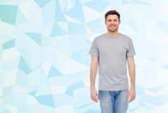 Hombre joven sonriente feliz en camiseta gris y vaqueros Imagen de archivo libre de regalías