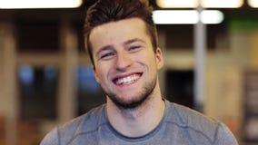 Hombre joven sonriente feliz en el gimnasio almacen de metraje de vídeo