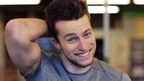 Hombre joven sonriente feliz en el gimnasio metrajes