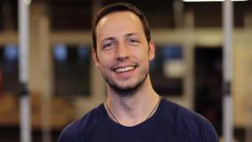 Hombre joven sonriente feliz en el gimnasio almacen de video