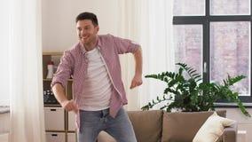 Hombre joven sonriente feliz que baila en casa almacen de video