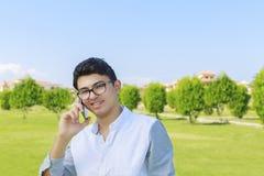 Hombre joven sonriente feliz que habla en al aire libre móvil Imagen de archivo
