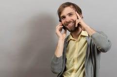 Hombre joven sonriente feliz que habla en el móvil aislado en gris Imagenes de archivo