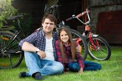 Hombre joven sonriente feliz que se sienta en hierba en el parque con el adolescente después de montar la bicicleta Foto de archivo