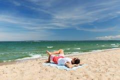 Hombre joven sonriente feliz que toma el sol en la toalla de playa Fotos de archivo