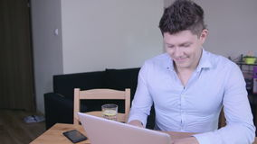 Hombre joven sonriente feliz que trabaja y que mecanografía en el ordenador portátil en casa metrajes