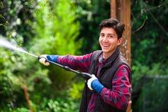 Hombre joven sonriente hermoso que lleva el rojo cuadrado del modelo que sostiene el arma de agua de alta presión, en un fondo de Fotos de archivo libres de regalías
