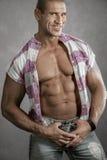 Hombre joven sonriente muscular contra fondo gris imagenes de archivo