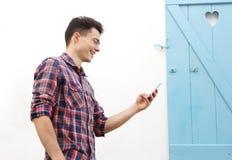 Hombre joven sonriente que camina afuera con el teléfono móvil Imagenes de archivo