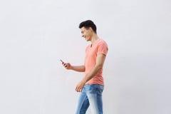 Hombre joven sonriente que camina y que mira el teléfono celular Foto de archivo