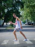Hombre joven sonriente que cruza la calle Individuo de moda en gafas de sol en un fondo borroso Concepto del carisma Copie el esp Imagen de archivo