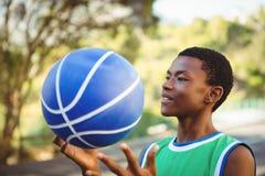 Hombre joven sonriente que juega con baloncesto Fotografía de archivo
