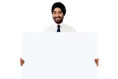 Hombre joven sonriente que lleva a cabo el tablero blanco de la muestra Imagen de archivo