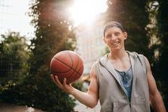 Hombre joven sonriente que lleva a cabo un baloncesto en corte Imagen de archivo libre de regalías