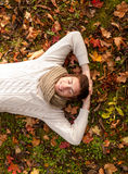 Hombre joven sonriente que miente en la tierra en parque del otoño Foto de archivo libre de regalías