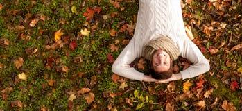 Hombre joven sonriente que miente en la tierra en parque del otoño Fotos de archivo