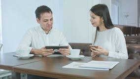 Hombre joven sonriente que muestra algo en su tableta al compañero de trabajo femenino que sostiene el teléfono durante almuerzo almacen de metraje de vídeo