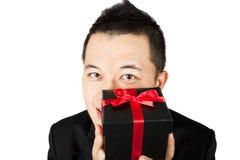 Hombre joven sonriente que ofrece un regalo Imagen de archivo