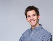 Hombre joven sonriente que presenta contra fondo gris Foto de archivo libre de regalías