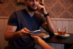 Hombre joven sonriente que presenta su célula Fotografía de archivo