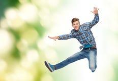Hombre joven sonriente que salta en aire Imagenes de archivo