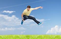 Hombre joven sonriente que salta en aire Fotografía de archivo