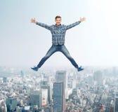 Hombre joven sonriente que salta en aire Fotografía de archivo libre de regalías