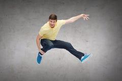 Hombre joven sonriente que salta en aire Imagen de archivo libre de regalías