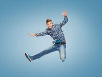 Hombre joven sonriente que salta en aire Fotos de archivo