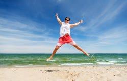 Hombre joven sonriente que salta en la playa del verano Imagenes de archivo