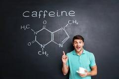Hombre joven sonriente que señala en la estructura química de la molécula exhausta del cafeína fotografía de archivo