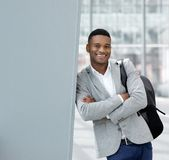 Hombre joven sonriente que se coloca en el aeropuerto con el bolso Fotos de archivo