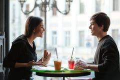 Hombre joven sonriente que se sienta en café con el jugo de consumición de la hermana Imagen de archivo libre de regalías