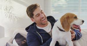 Hombre joven sonriente que se sienta en el sofá que frota ligeramente su perro casero 4K 4k metrajes