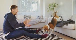 Hombre joven sonriente que se sienta en la comida de alimentación de la tierra al perro casero juguetón 4K 4k almacen de metraje de vídeo