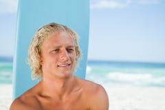 Hombre joven sonriente que se sienta en la playa con su tabla hawaiana Foto de archivo