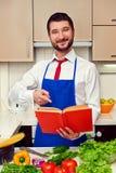 Hombre joven sonriente que señala en el libro de cocina Fotografía de archivo