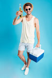 Hombre joven sonriente que sostiene un bolso más fresco y que bebe la cerveza Imagen de archivo