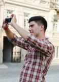 Hombre joven sonriente que toma una fotografía fotos de archivo