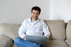 Hombre joven sonriente que usa el ordenador portátil en casa Imagen de archivo libre de regalías