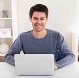 Hombre joven sonriente que usa una computadora portátil Foto de archivo libre de regalías