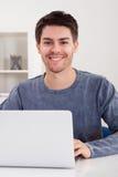 Hombre joven sonriente que usa una computadora portátil Imagen de archivo
