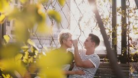 Hombre joven sonriente relajado y mujer de la cámara lenta que hablan en el banco de parque del otoño que disfruta de día soleado metrajes