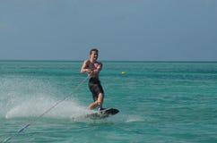 Hombre joven sonriente Wakeboarding en las aguas costeras de Aruba imagen de archivo libre de regalías