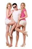 Hombre joven sonriente y dos muchachas juguetonas Fotografía de archivo libre de regalías
